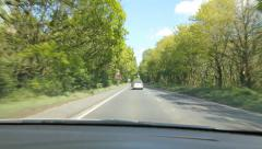 Driving through sunlit forest in the UK. Flickering light. - stock footage