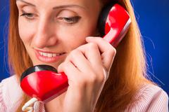 Redhead woman with red telephone Stock Photos