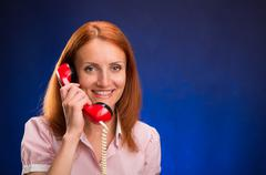 Redhead girl with red telephone Stock Photos