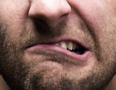 Closeup of mouth of very stressed man - stock photo
