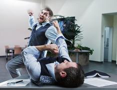Businessmen fighting in the office Kuvituskuvat