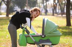 Young mother carrying baby in autumn park - stock photo