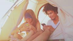 Young couple sits in tent and communicates with their friends by the phones - stock footage