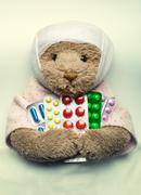 Ill teddy bear in bed - stock photo