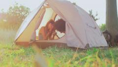 Young, different racial couple has a rest in tent and watches news in phone Stock Footage