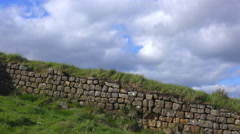 A time lapse of clouds moving behind Hadrians Wall in England. Stock Footage