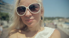 Happy girl in sunglasses takes selfie while walking along the French Riviera in - stock footage