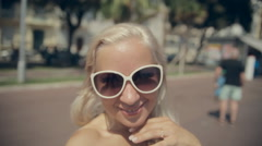Happy girl in sunglasses takes selfie while walking along the French Riviera - stock footage