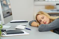 Tired Office Woman Leaning on her Desk - stock photo