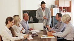 Boss and stressed co-workers on meeting indoors - stock footage