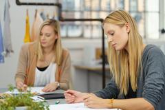 Fashion Stylists Sketching New Designs on Papers - stock photo