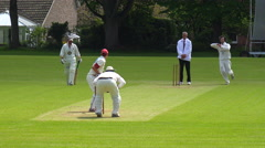 The sport of cricket is played on a green grass pitch in England. - stock footage