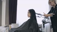 Stock Video Footage of Attractive asian ethnicy girl have a curling procedure for her straight hair