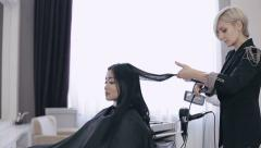 Stock Video Footage of Attractive asian ethnicy girl have a curling procedure for her straight hair in