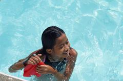 Girl immerses self in pool water Stock Photos