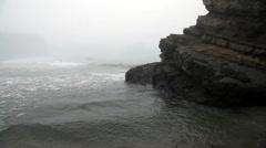 Fog Shrouded Waves Moving Around Large Rock Stock Footage