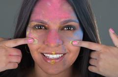 Beautiful young brunette girl painting her face with colorful powder Stock Photos