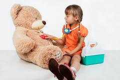 Baby is playing doctor, treats a bear Stock Photos