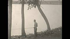 Vintage 16mm film, 1938, Illinois, Reed lake man fishing from shore - stock footage