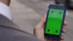 4K Close up of hand using a smartphone with green screen display outdoors - stock footage