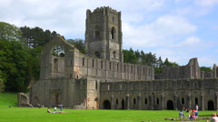 An abandoned cathedral abbey of Fountains with people having picnics foreground. Stock Footage