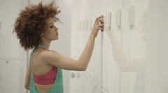 Young woman opening locker in gym changing room Stock Footage
