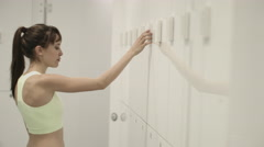 Young woman opening locker in gym changing room - stock footage