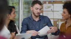 4K Young casual business group looking at paperwork & discussing ideas Stock Footage