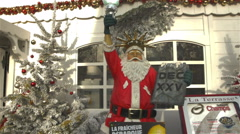 Funny Santa Claus In Front Of A Restaurant, In The Position Of Statue Of Liberty Stock Footage