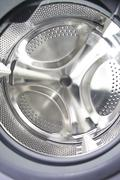 Closeup of an empty washing machine drum - stock photo