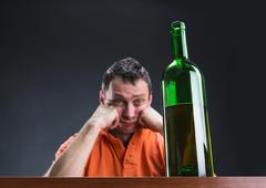 Drunk alcohol addict looks at the bottle - stock photo