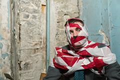 Man with stripped duct tape over body in old house - stock photo