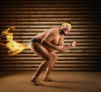 Very strange naked man farts by fire Stock Photos