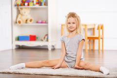 Little girl doing split on the floor Stock Photos