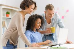 Three young people are collaborating in the office - stock photo