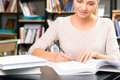 Young girl doing her home assignment - stock photo