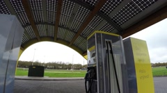 Footage of an electric vehicle charging station with highway in background 4k - stock footage