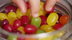 Close up of a piece of candy being taken from a sweet jar, in slow motion Stock Footage