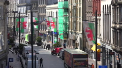Establishing shot of a narrow street lined with Welsh flags in downtown Cardiff, Stock Footage