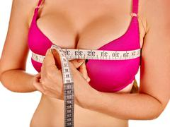 Girl in lingerie measures her breast measuring tape - stock photo