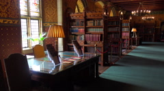 An elegant interior of a mansion with old books and chandeliers. - stock footage