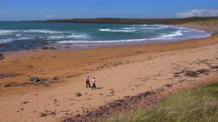 People walk along a beautiful beach on the coast of Southern Wales. Stock Footage