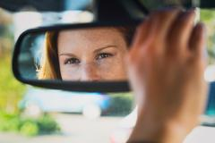 Car Driver Adjusting Mirror - stock photo