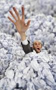 Businessman sinking in big heap of crumpled papers - stock photo