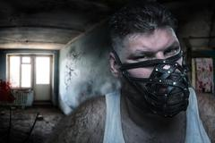Adult agressive man in muzzle in bloody room - stock photo