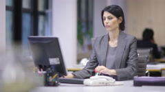 Women Leaders, Young Woman In Business Suit. Sitting in an office at her desk wo - stock footage