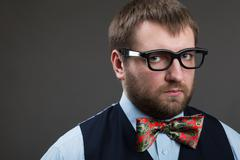 Suspicious man in glasses looks at you over grey background - stock photo