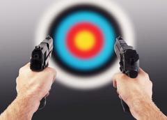 Man shooting with two guns - stock photo