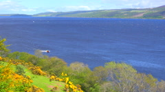 An establishing shot of Loch Ness, Scotland with speedboat passing. Stock Footage