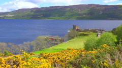 An establishing shot of Loch Ness castle, Scotland with speedboat passing. Stock Footage